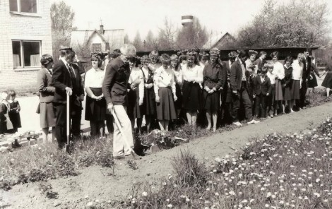 Imants Ziedonis stāda savu rozi pie Dundagas vidusskolas 28.05.1985. Aiz viņa izlaiduma klase.