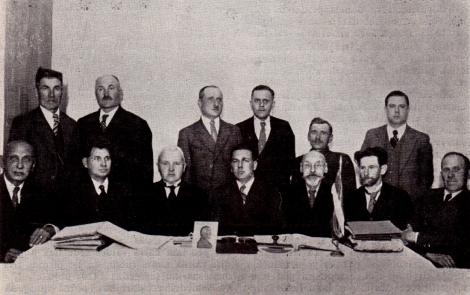 Sēž no kreisās puses 1. — pad. loc. Fricis Munkevics, 2. — pad. loc. Jānis Šultners, 3. — pad. pr-js Valdis Legzdiņš, 4. — Latv. tautas bankas revidents-instrukt. Heinrichsons. 4. — vaid. pr-js Kārlis Eichlers, valdes pr-ja biedrs - sekretārs Jānis Drafens un valdes loceklis - kasieris Alfrēds Derkevics. Stāv no kreisās: 1. — padomes loc. Ernests Blumbergs, 2. — pad. loc. (pr-ja biedrs) Pēteris Ērglis, 3. — revīz. kom. pr-js Ģirts Emars, 4. — revīz. komis. loceklis Kārlis Feldmanis un grāmatvedis-darbvedis Jānis Liepkalns.