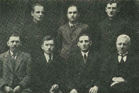 """Dundagas lauksaimniecības biedrības """"Druva"""" valde 1930. gadā. Sēd no kreisās: loceklis H.Rītenbergs, K.Nerliņš, priekšsēdētājs J.Hermansons un kasieris V.Legzdiņš. Stāv no kreisās: valdes loceklis E,Klebers, agr. E.Mālkalns, sekretārs E.Vītols."""